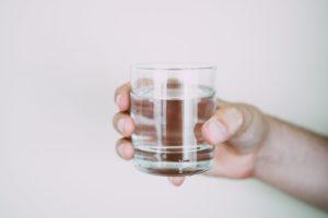 コップに入った水を持つ