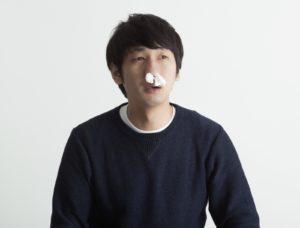 風邪の初期症状で鼻栓をしている男性
